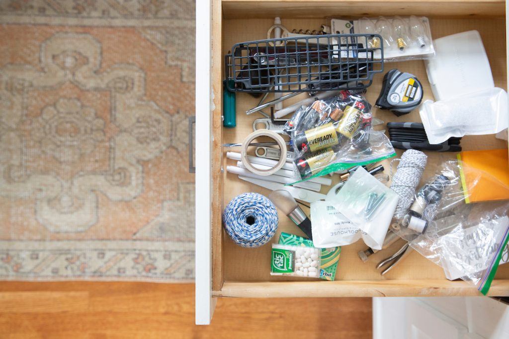 The first step is to remove all the contents from your junk drawer.